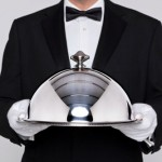 Waiter holding a silver cloche